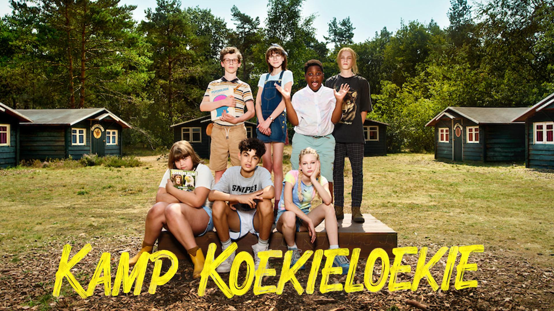 Kamp Koekieloekie. Zeven kinderen staan en zitten in een veld in een bos.