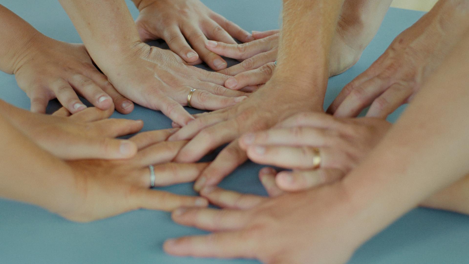 Tien handen leunen verstrengeld op een lichtblauwe ondergrond.