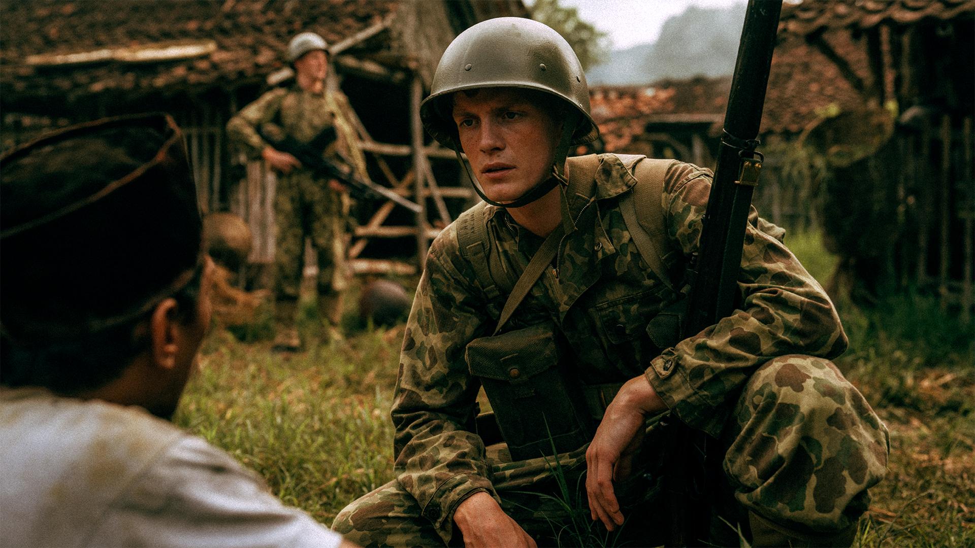 De Oost. Een jonge soldaat met een ouderwetse, bolle helm op zijn hoofd, knielt tegenover een Indonesische man.