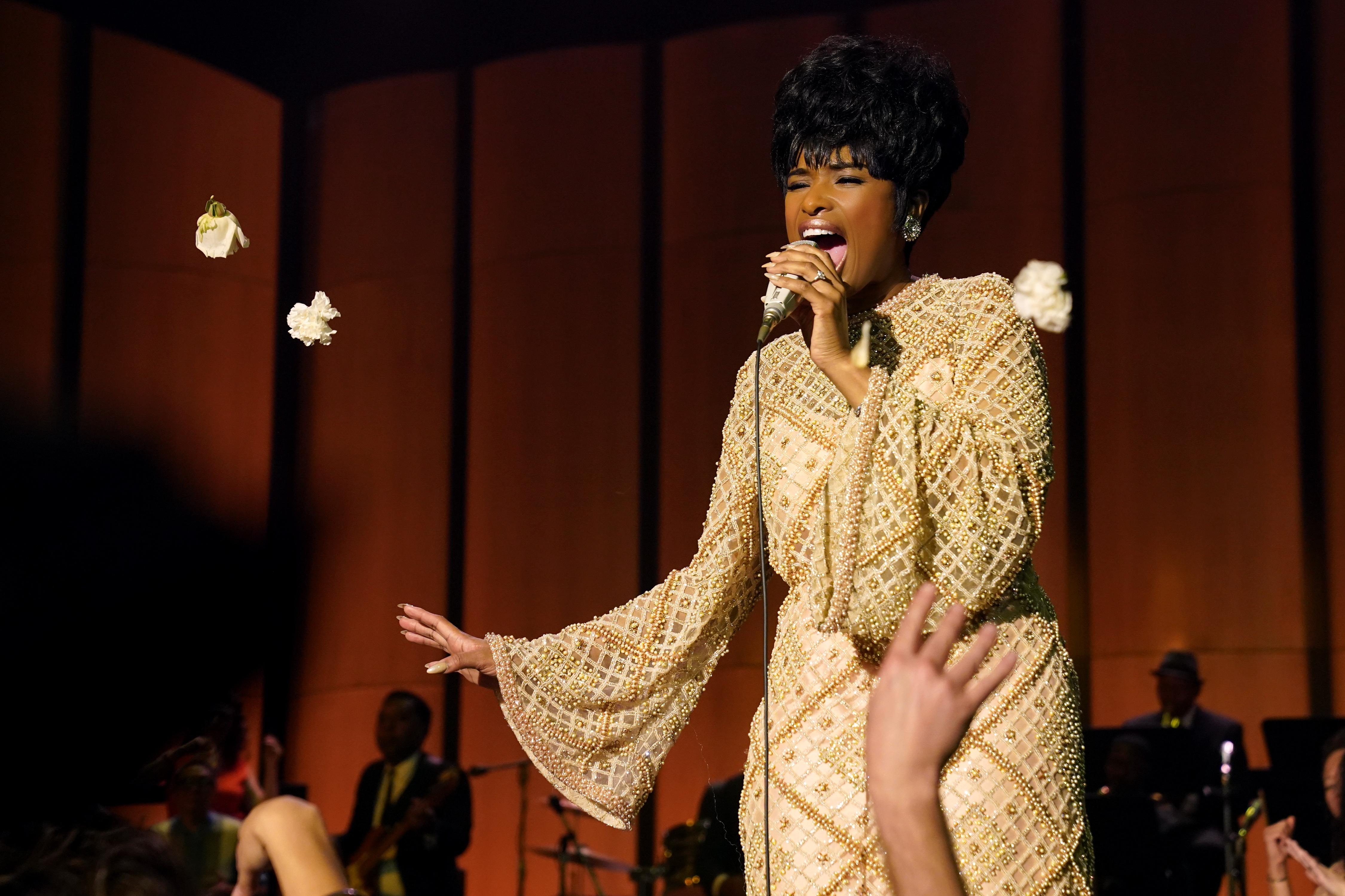 Respect (OV). Een knappe, donkere vrouw met kort haar staat op een podium in een gouden jurk en zingt de longen uit haar lijf.