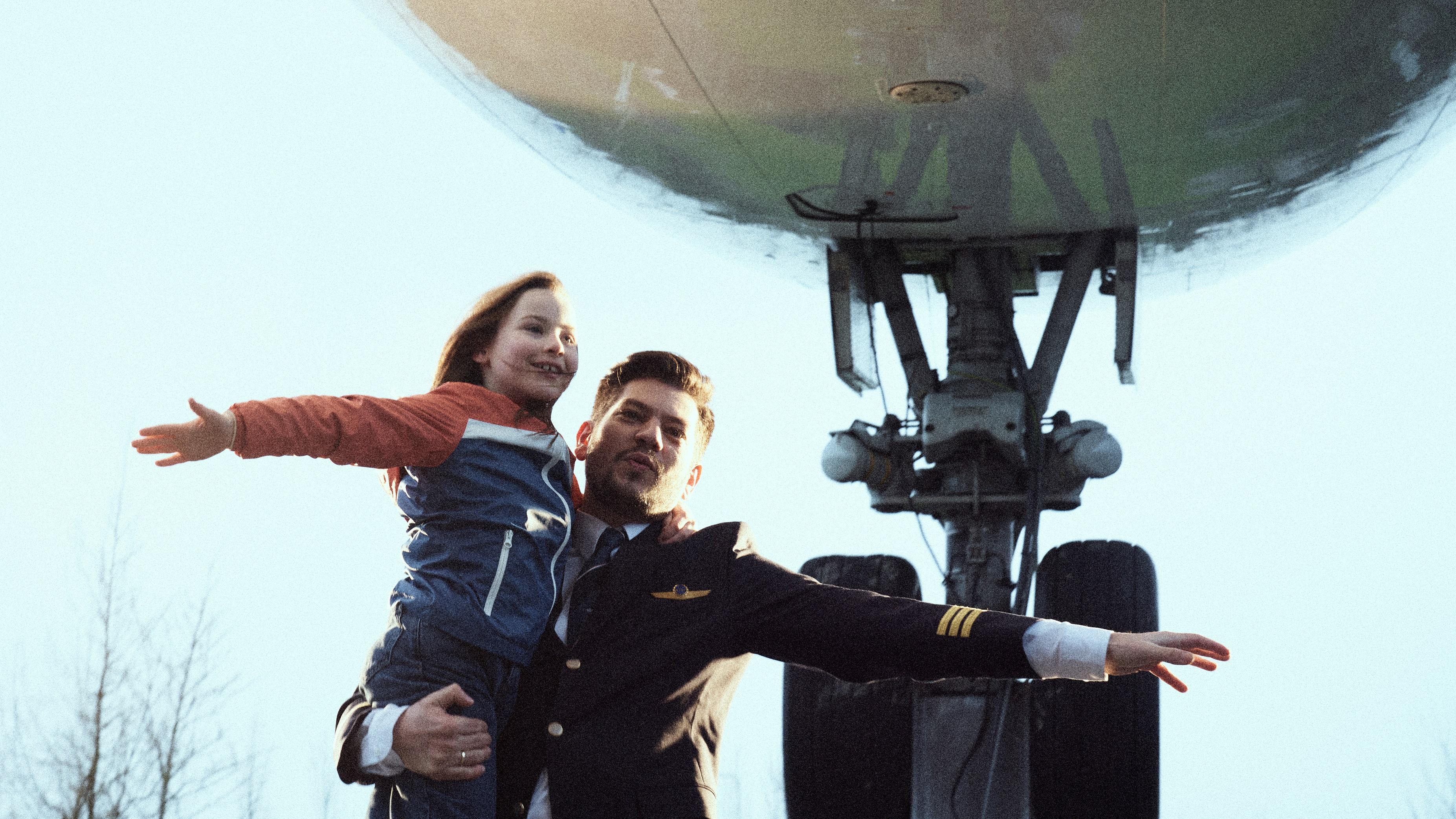 Een piloot staat met een klein meisje in zijn armen onder een stilstaand vliegtuig. Ze spreiden hun armen wijd als de vleugels van een vliegtuig.