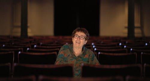 Heddy Honigmann, een vrouw met kort, bruin haar en een bril, zit in een theaterzaal.