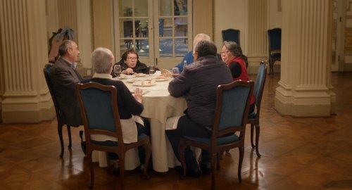 Zes oudere mensen zitten aan een ronde tafel te eten.