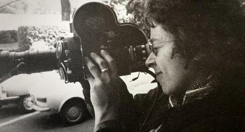 Een oude zwart-witfoto van een vrouw met donkere krullen, die door een camera kijkt.