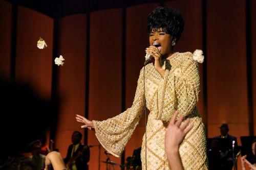 Een knappe, donkere vrouw met kort haar staat op een podium in een gouden jurk en zingt de longen uit haar lijf.