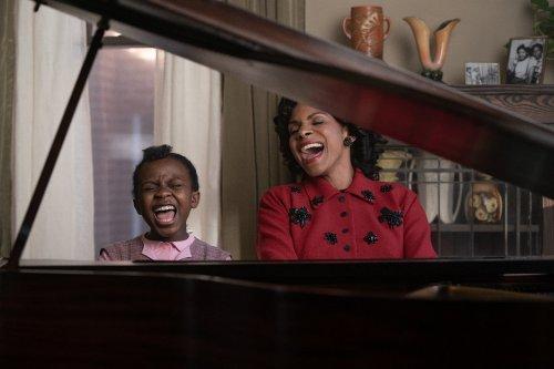 Een vrouw en een meisje zitten achter een piano en zingen luidkeels.