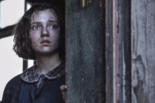 Een donkerharig meisje met een vies gezicht kijkt ontgoocheld voor zich uit vanuit een barak.