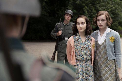 Twee donkerharige meisjes staan tegenover een soldaat. Achter hen staat een tweede soldaat met een geweer.