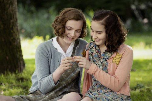Twee donkerharige meisjes met een jodenster op hun kleding zitten glimlachend samen in het gras.