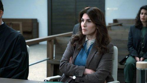 Een vrouw met lang, donker haar en nette kleding zit met haar armen over elkaar in een rechtszaal.