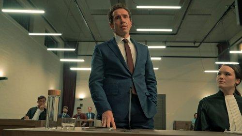 Een man in pak staat naast zijn advocaat in een rechtszaal en kijkt serieus voor zich uit.