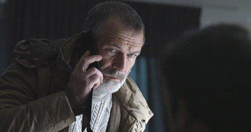 Een man met grijs haar, een snor en een korte baard kijkt ernstig terwijl hij aan de telefoon is.