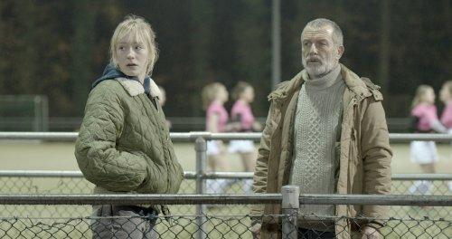Een blonde vrouw en een grijze man staan met jassen aan naast een hockeyveld.