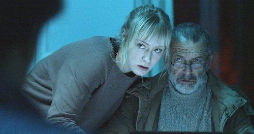 Een blonde vrouw en een grijze man kijken ernstig naar een persoon voor hen.