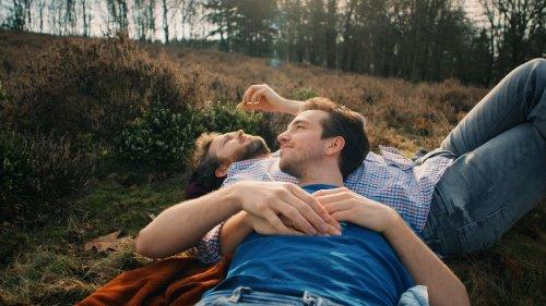 Een man man met een blauw t-shirt aan en een trouwring om ligt met z'n hoofd op de borst van een man met een geruit bloesje. Ze liggen op de hei.