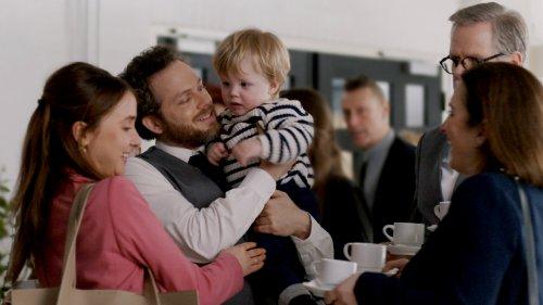 Vier volwassenen staan bij elkaar met kopjes koffie in de hand. Een man met een baard houdt een blond jongetje vast en lacht naar hem.