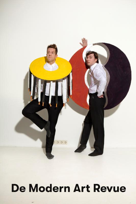 De Modern Art Revue. Twee mannen staan met gekleurde kunstvoorwerpen voor een witte muur.