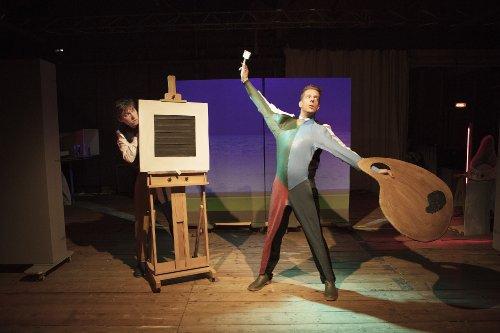 Twee mannen staan op een podium. Eén van hen doet dramatisch een schilder na, terwijl de ander zich verstopt achter een doek op een schildersezel.