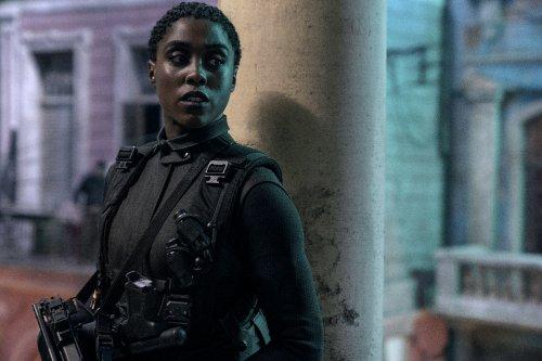 Een gewapende vrouw staat met haar rug tegen een pilaar en kijkt alert opzij.