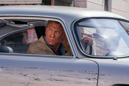 James Bond, een man met blond haar en blauwe ogen, zit in een gehavende auto. Zijn neus bloedt en hij kijkt uit het raam.