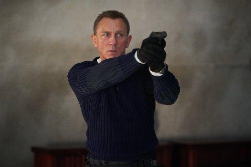 James Bond, een man met blond haar en blauwe ogen, heeft een pistool getrokken en kijkt gespannen vooruit.