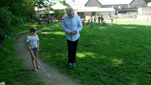 Fred, een man met wit haar, loopt naast een meisje met een blinddoek dat met een taststok loopt.