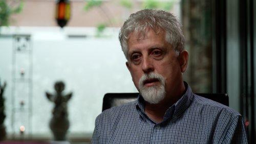 Fred, een man met een wit ringbaardje en rode ogen, zit in een woonkamer te praten.