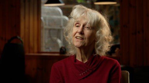 Truus, een vrouw met wit haar, zit in een woonkamer te praten.