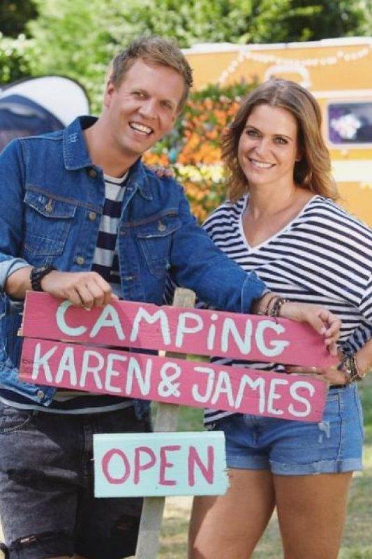 Een bordje met daarop Camping Karen & James Open. De twee presentatoren staan erachter met een grote glimlach.