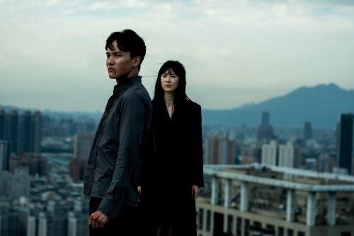 Een jonge Aziatische man en vrouw staan boven een grote stad. De man heeft bloed op zijn gezicht.