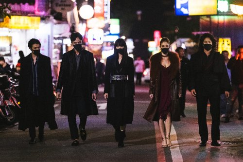 Vijf donkerharige, jonge mensen met mondkapjes op lopen naast elkaar door een fel verlichte, Aziatische stad.