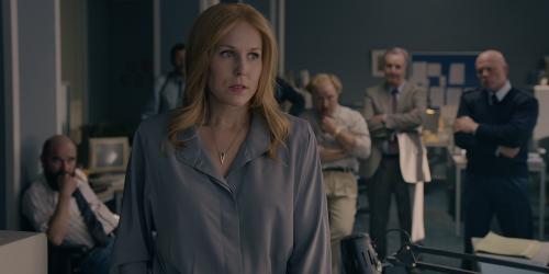 Een vrouw met lang, roodblond haar in een grijze blouse staat in een kantoor met mannen die met serieuze gezichten luisteren.