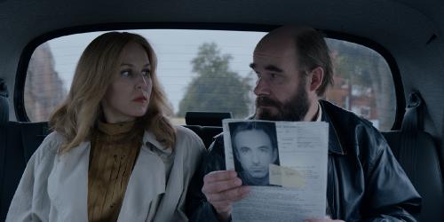 Een roodblonde vrouw en kalende man zitten op de achterbank van een auto en kijken elkaar veelbetekenend aan. De man houdt een dossier vast met daaraan een zwart-wit-foto van een man.