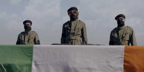 Drie mensen in IRA-uniform met bedekte gezichten staan achter een Ierse vlag.