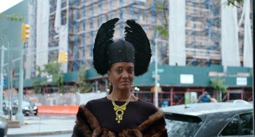 Een zwarte vrouw staat trots in New York. Ze draagt een  hoofddeksel met zwarte veren, een gouden ketting en een stola van bont.