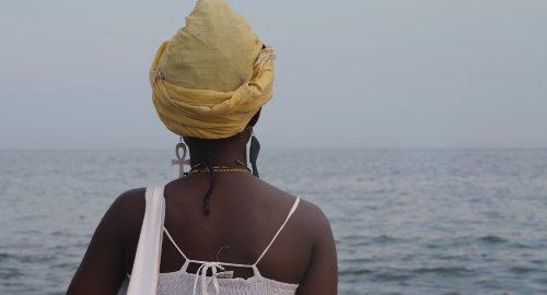 Een zwarte vrouw met een gele tulband kijkt uit over het water.
