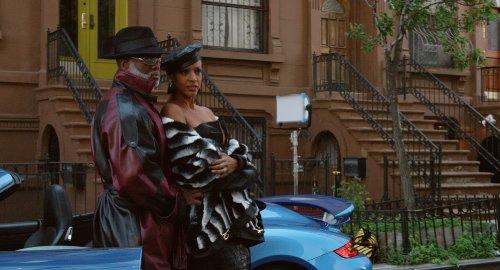 Een zwarte man en vrouw poseren in mooie kleding en met hoeden op in een woonwijk in New York.