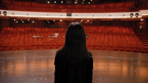 Een vrouw met donker haar kijkt vanaf een podium uit over een lege zaal.
