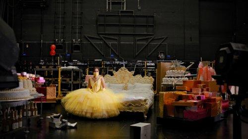 Een vrouw zit in een gele jurk met een bijpassend mondkapje backstage tussen de attributen.