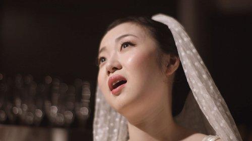 Een vrouw met een sluier staat zingend op een podium.