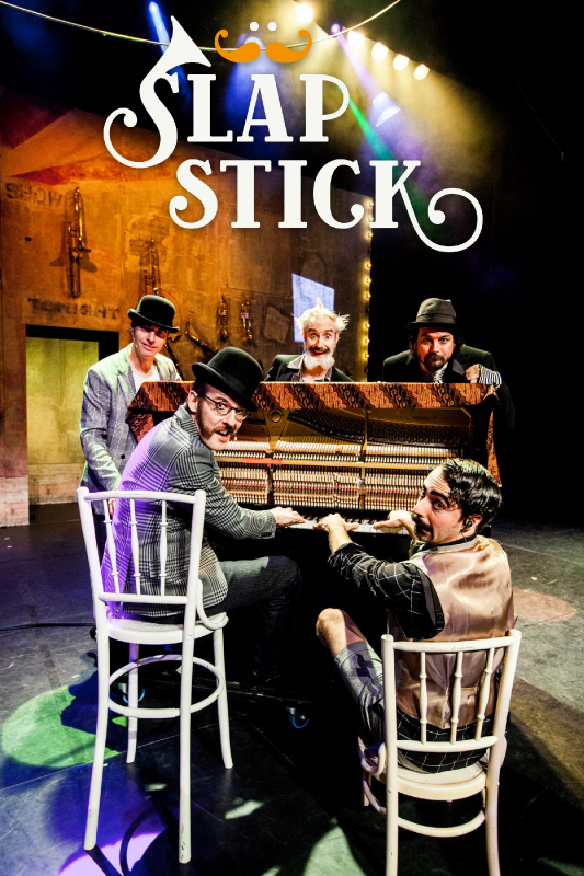 Släpstick. Vijf mannen met snorren en bolhoeden zitten rond een vleugel op een toneel.