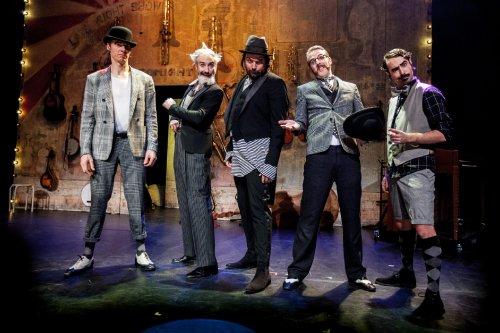 Vijf mannen in ouderwetse kleding zoals gilets en bolhoeden staan op een podium.