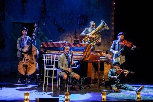 Een vijfkoppige theatermuziekgroep op het toneel.
