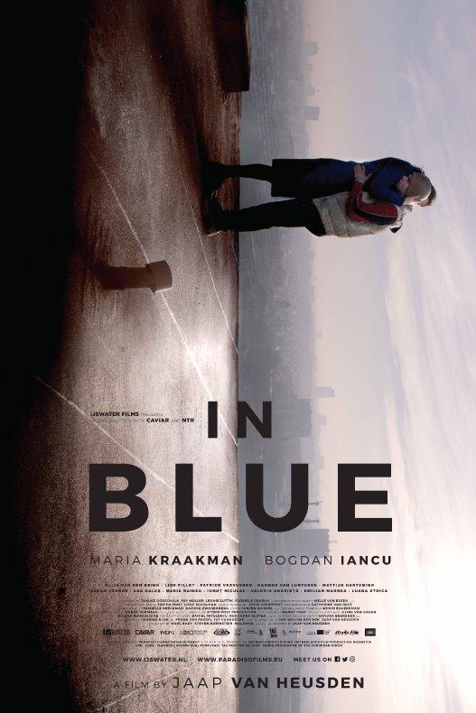 In Blue. Het gekantelde beeld van een man en een vrouw die op het dak van een gebouw elkaar innig vasthouden.