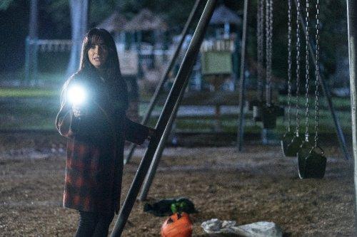 Een vrouw staat in het donker met een zaklamp bij lege schommels waar een fietshelmpje op de grond licht.