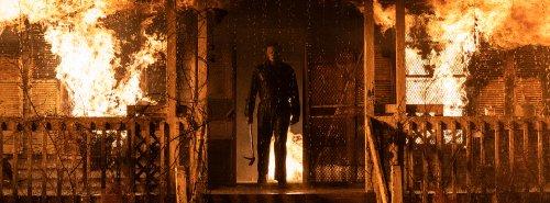 Temidden van een brandende veranda staat een man tussen de vlammen.
