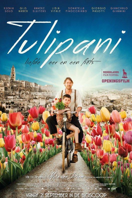 Tulipani. Een man fietst met een jonge jongen op de stang tussen de tulpen door in een Italiaans landschap.