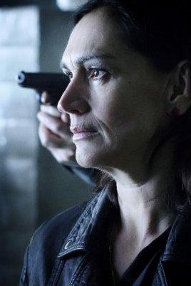 Penoza V. Carmen kijkt strak voor zich uit. Achter haar houdt iemand een pistool gericht.