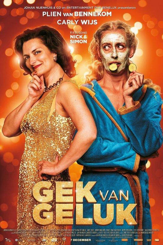 Gek van geluk. Een vrouw in gouden glitterjurk staat naast een vrouw in badjas met een gezichtsmasker en twee plakjes komkommer.