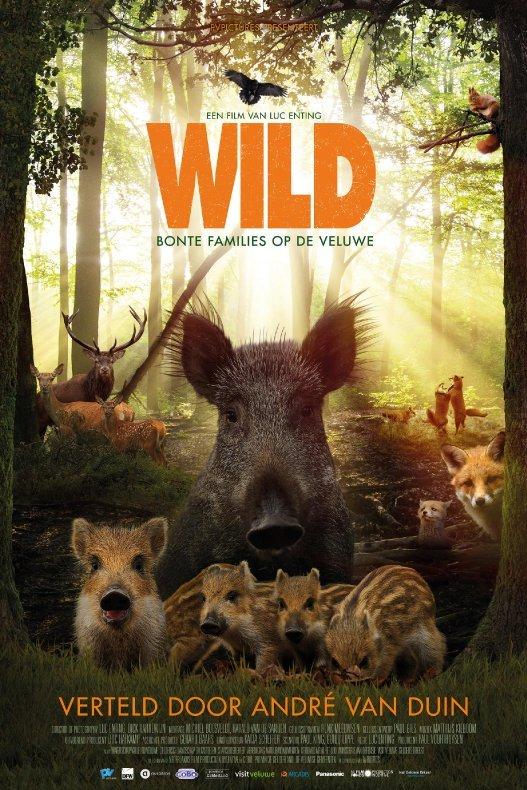 Wild. Bonte families op de Veluwe. Een everzwijn staat met haar jongen tussen twee hoge bomen. Achter hen kijken verschillende vossen en herten op.